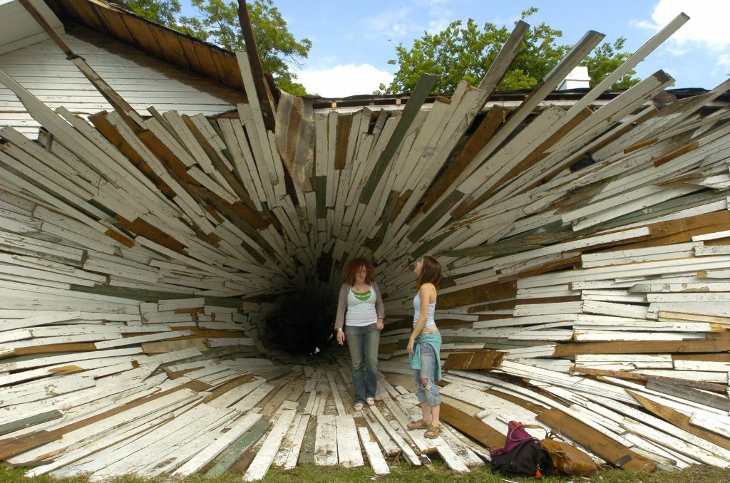 "Lindsey Hardin, left, and Samantha Santoski walk through ""inversion"", a sculpture by Dan Havel and Dean Ruck, Wednesday, May 4, 2005, in Houston. Havel and Ruck are transforming two Art League houses into a funnel-like vortex between two houses, where the exterior skin of the home will be peeled back beginning on the west wall and narrowed into a narrowing spiral that ends on the east wall. (AP Photo/Houston Chronicle, Brett Coomer)"